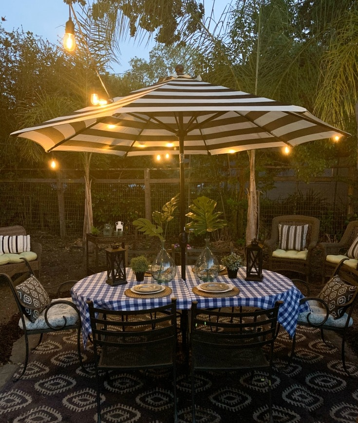 beautiful outdoor table with striped umbrella and picnic table cloth