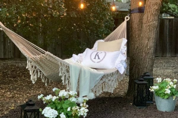 backyard hammock refresh with flowers and string lights
