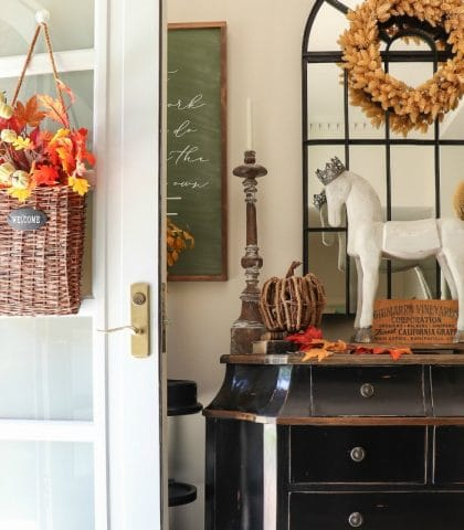 Warm fall botanical leaves and wreath decorate the door and entryway