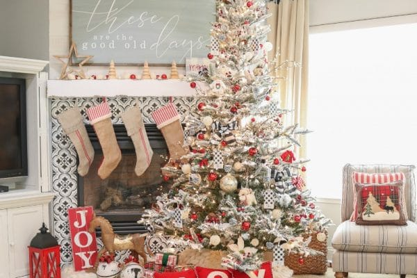 Beautiful flocked decorated realistic artificial Christmas trees with red and black decorations by the fireplace hung with burlap stockings