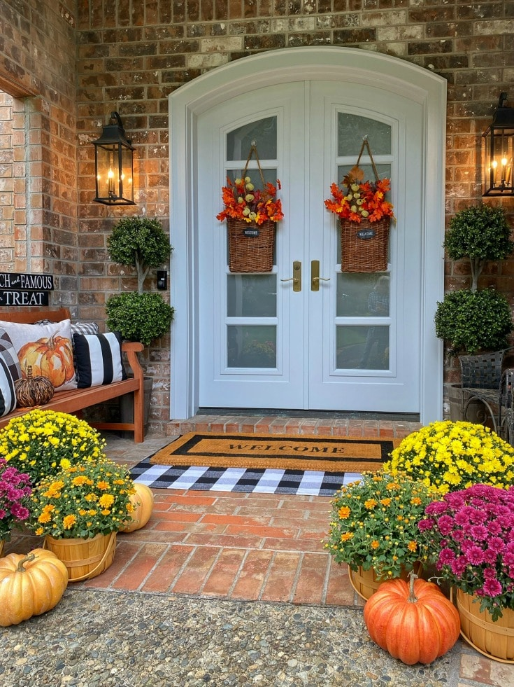 Colorful mums, pumpkins and baskets of rich autumn leaves create inviting entrance to fall front porch