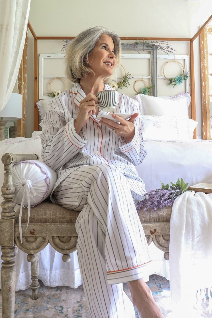 woman with coffee sitting at the foot of her bed