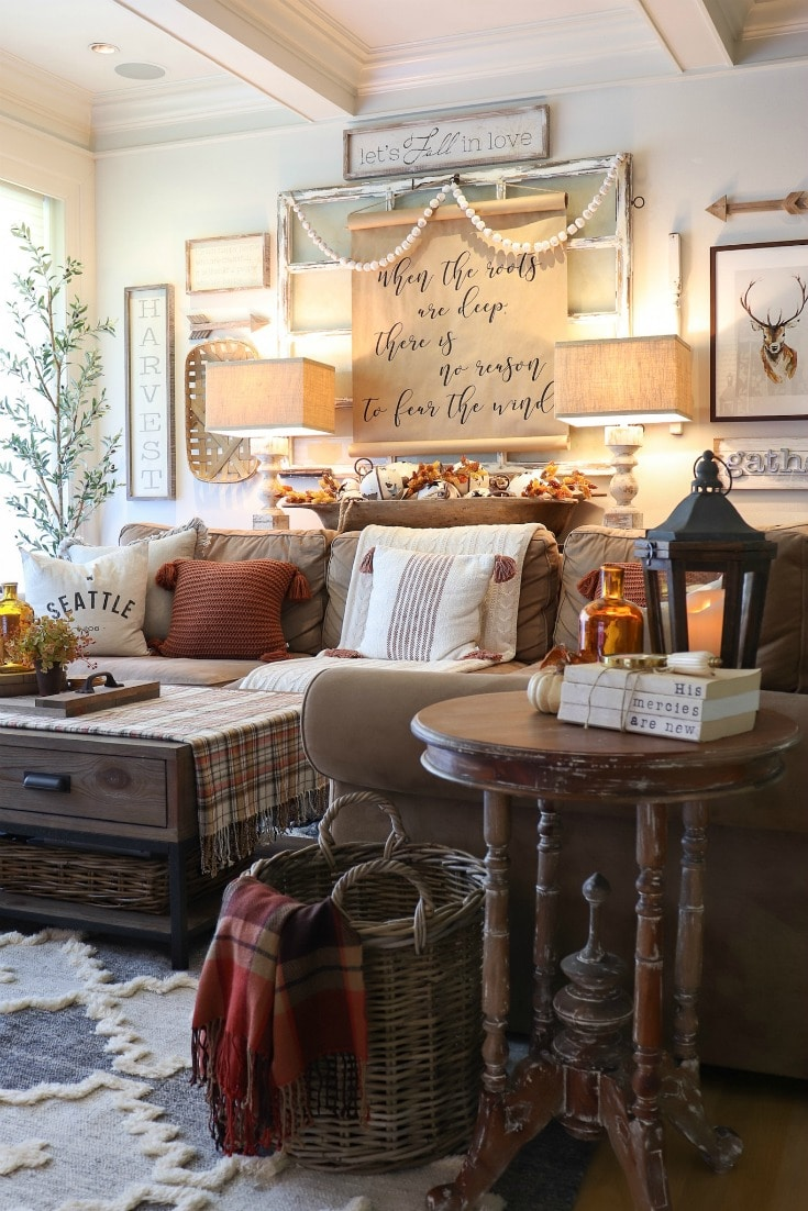 Rich hues, warm plaid blankets, and layers of textured decor create inviting fall living room decor