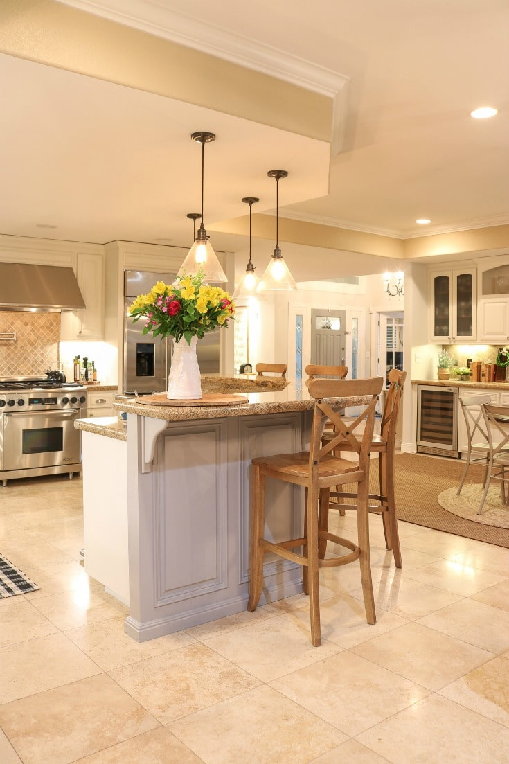 white painted kitchen cabinets in large great room with hanging pendent light lights and shiny stone floor