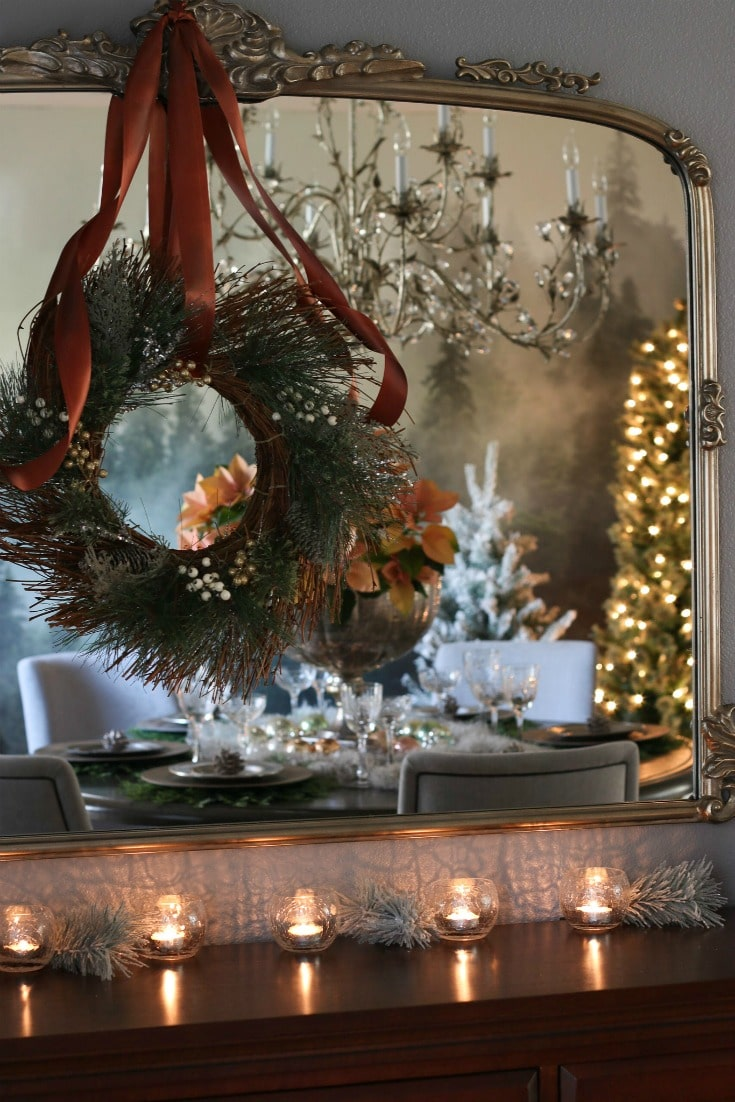 antique detailed mirror with holiday wreath reflecting beautiful festive dining room