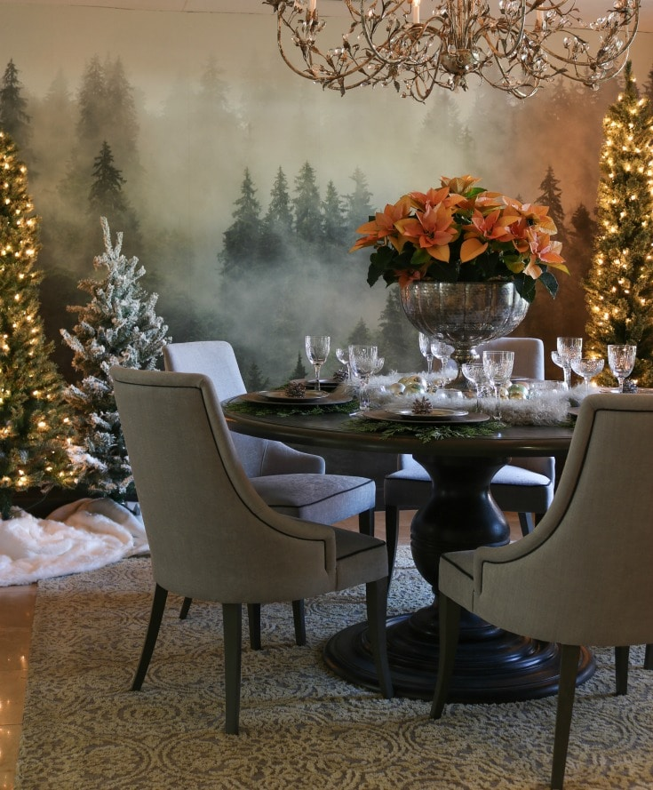 holiday dining room decor is extra festive with backdrop of forest wall mural and twinkling Christmas trees
