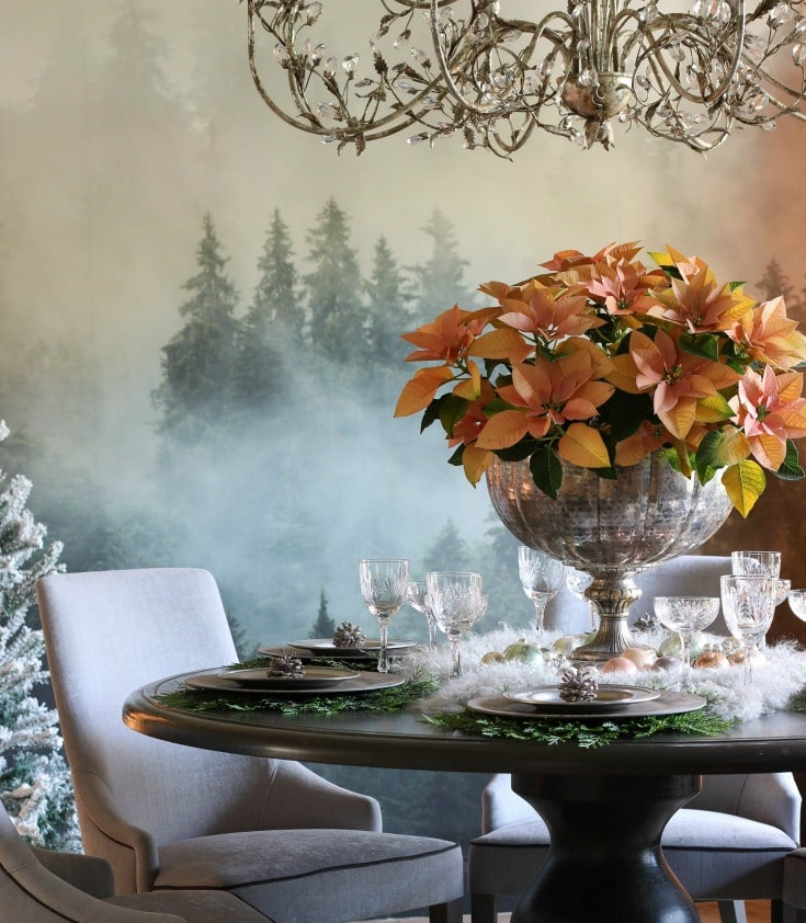 natural elements like wood table and evergreen placemats contrast with elegant crystal chandelier and glasses