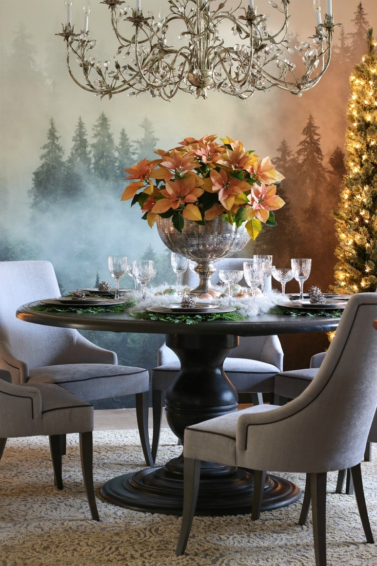 gorgeous dining room with forest mural pink poinsettia centerpiece crystal chandelier and grey upholstered chairs