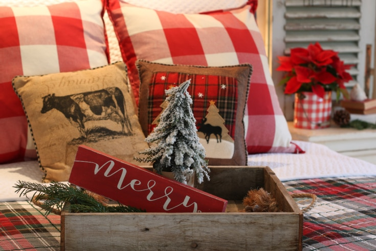 Christmas themed tray with mini trees and festive sign on top of plaid bed