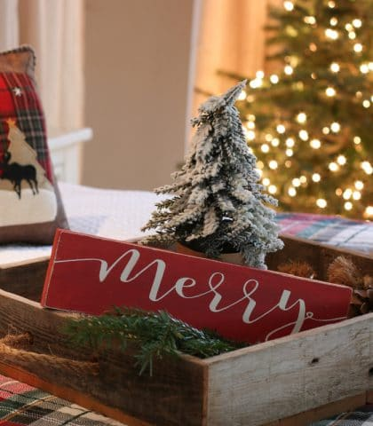 Natural rustic bed tray evergreen and red merry Christmas sign with sparkle of Christmas tree lights
