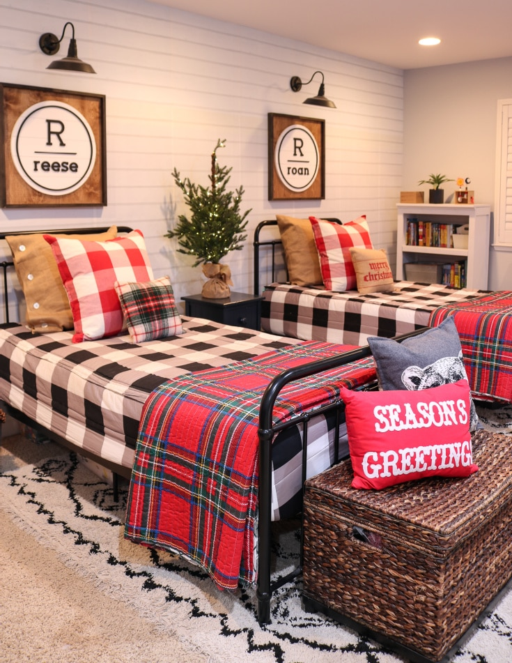 kids bedroom decorated for Christmas with plaid accents and festive pillows/bedding