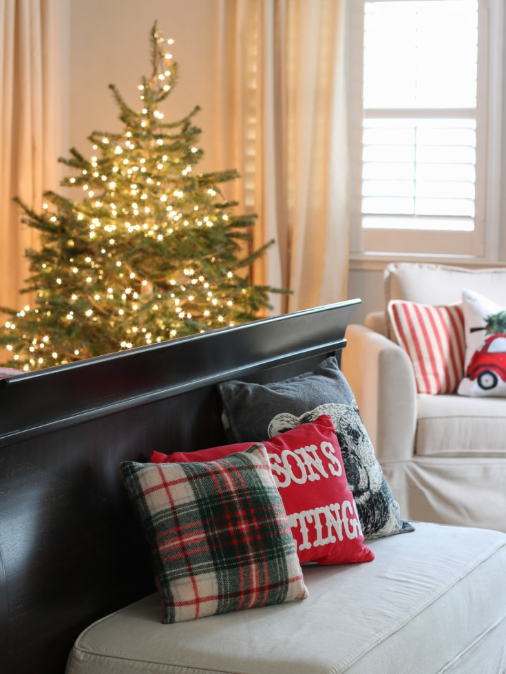bench in Christmas bedroom with festive pillows and Christmas tree in background