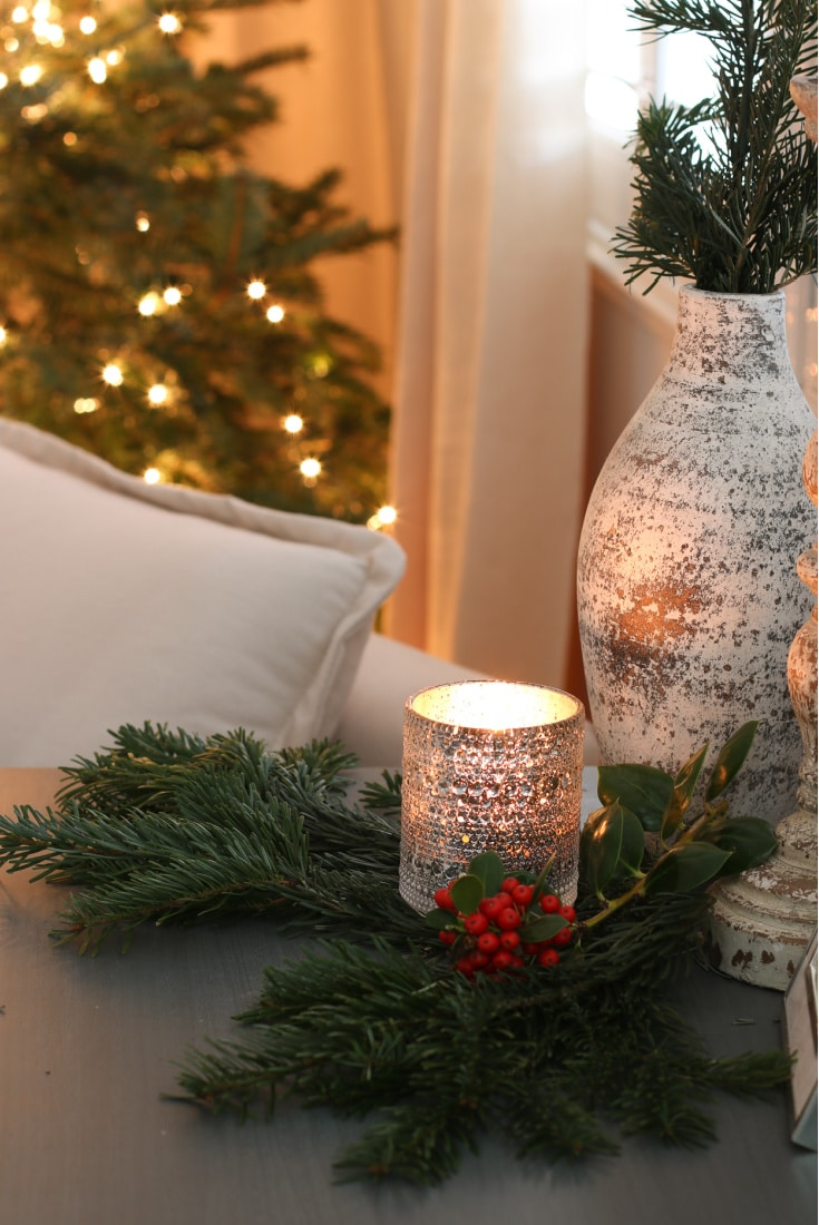 holiday vignette with candle, pine tree branches and a vase