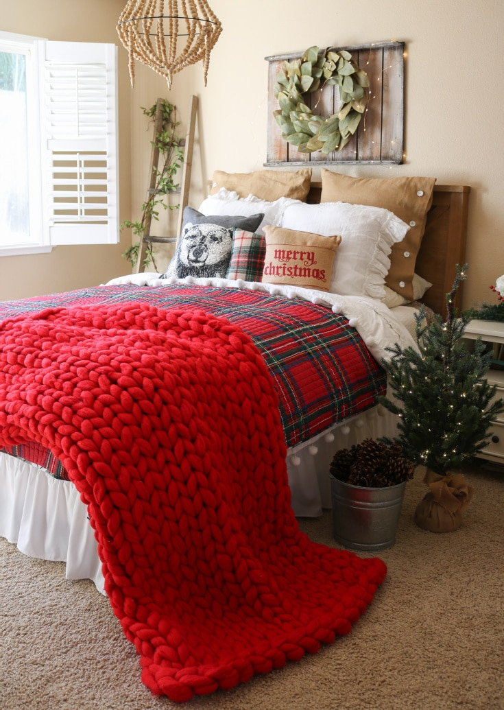 red chunky knit blanket on top of holiday bed