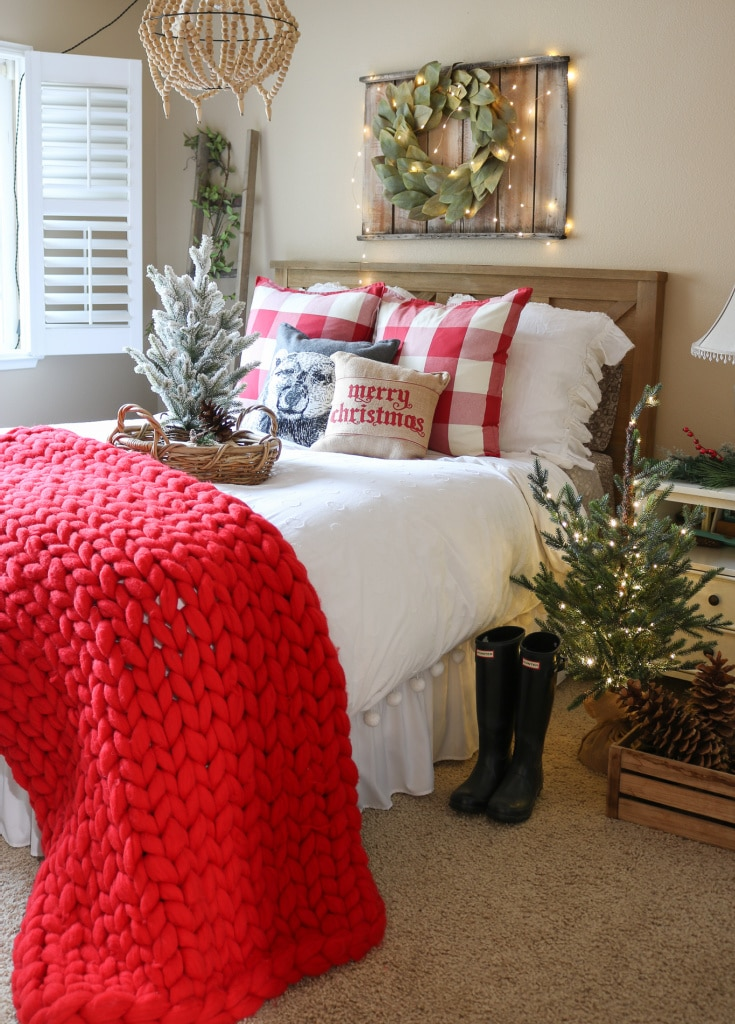 guest bedroom decorated for christmas with red chunky knit throw and mini christmas trees