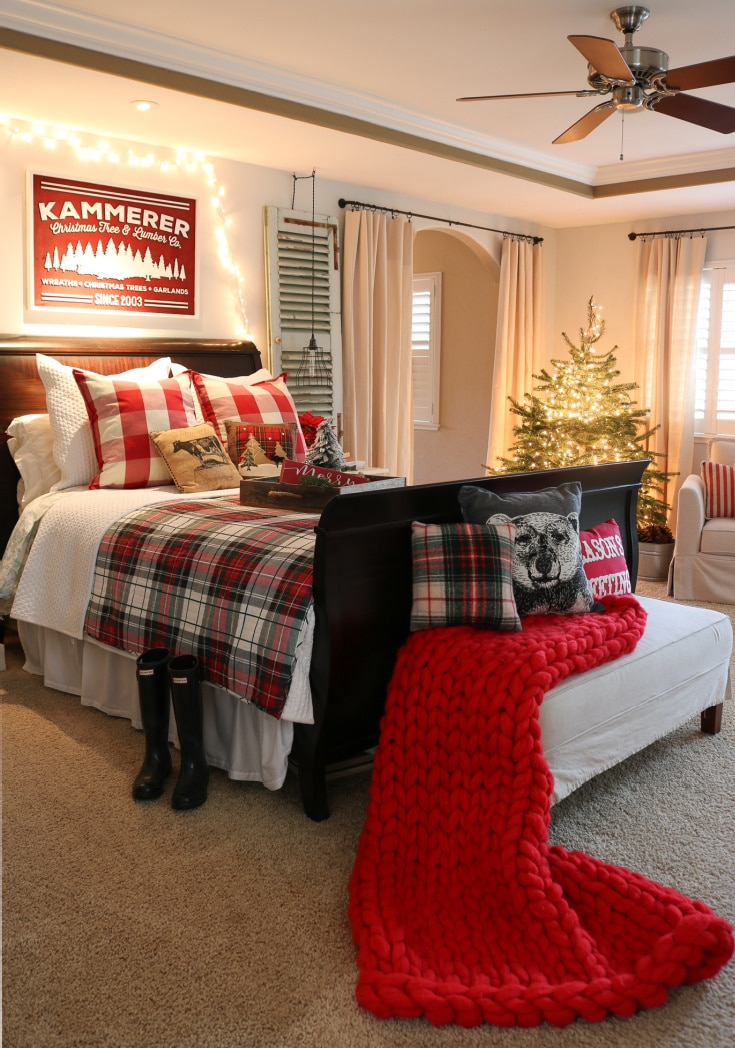 farmhouse christmas master bedroom with red plaid details and chunky blanket