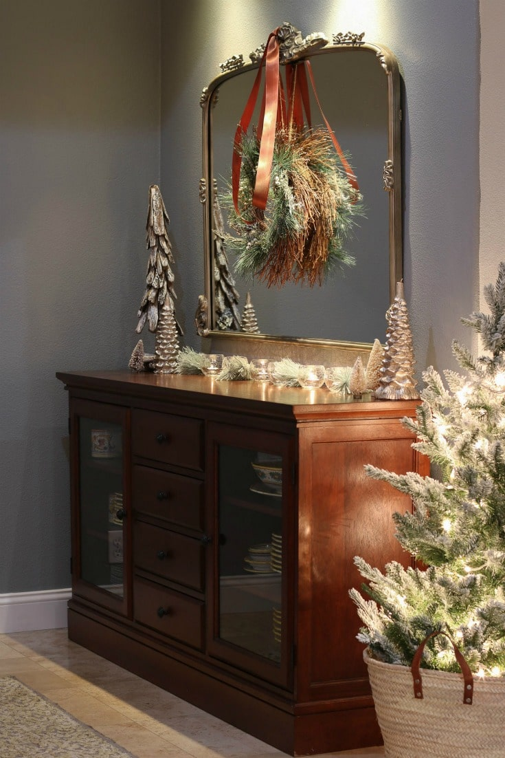 elegant dining room buffet with elegant mirror and mini Christmas tree in a basket