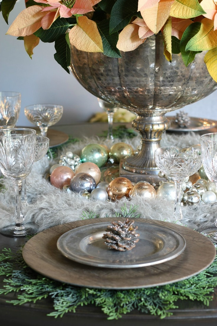 place setting detail with evergreen placemat wood charger pewter plate and glitter pinecone