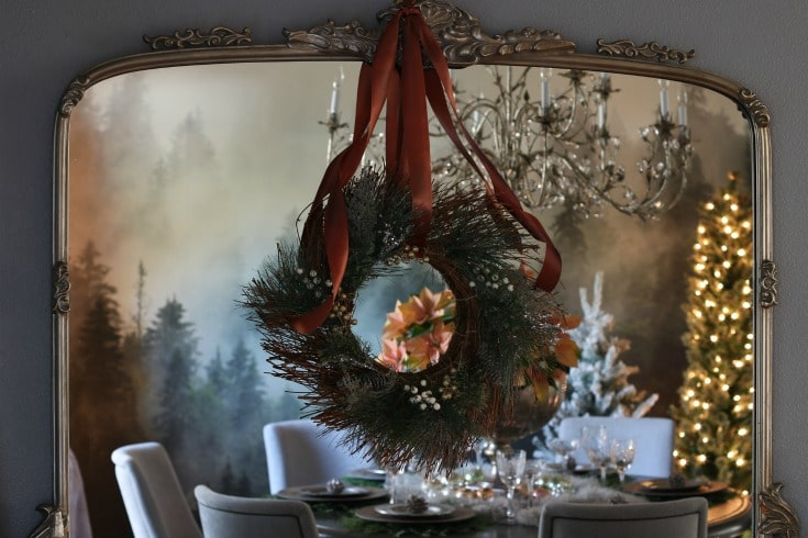 wreath with rust colored satin ribbon layered over a mirror reflecting sparkle of Christmas tree lights