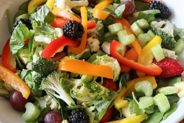 Colorful green vegetables and colorful fruits mixed in white ceramic bowl to eat healthy