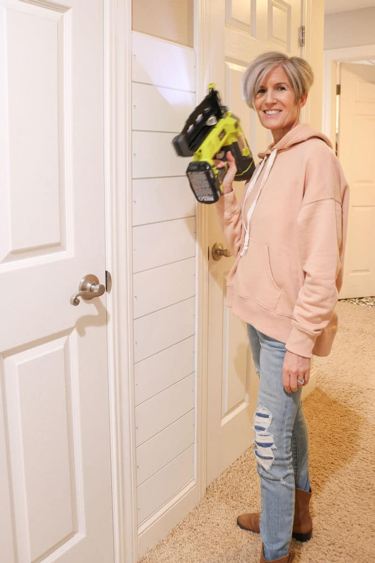 woman posing with nail gun in front of shiplap walls