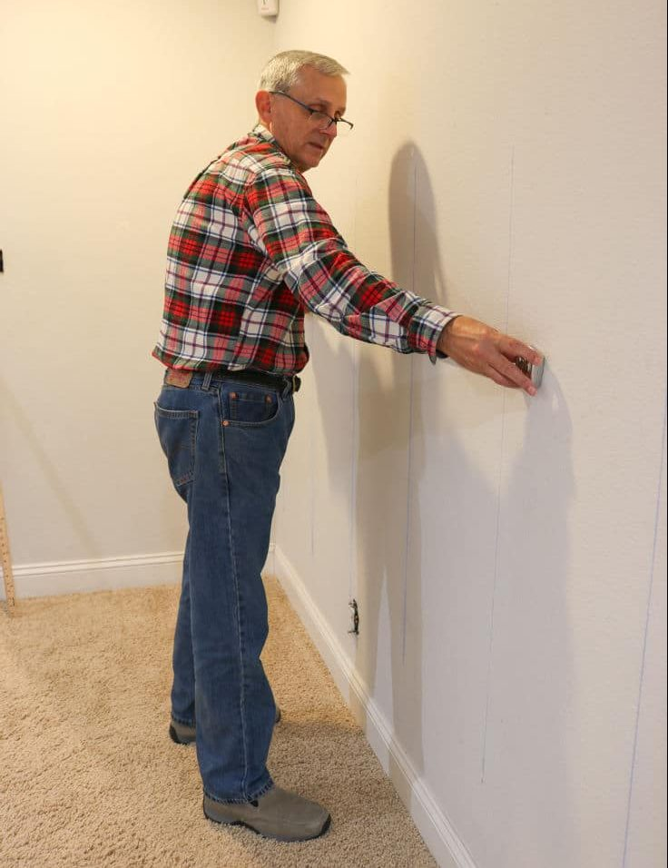 man measuring wall to find studs for shiplap wall