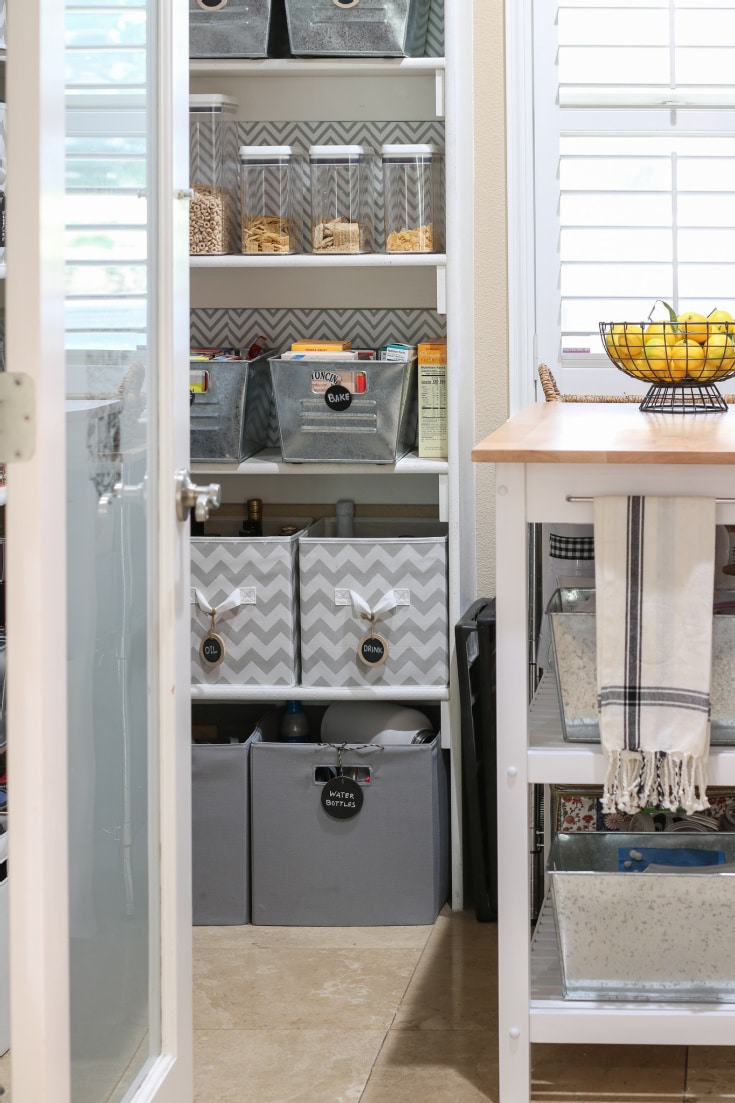 grey and white canvas organizing bin in white walk-in pantry