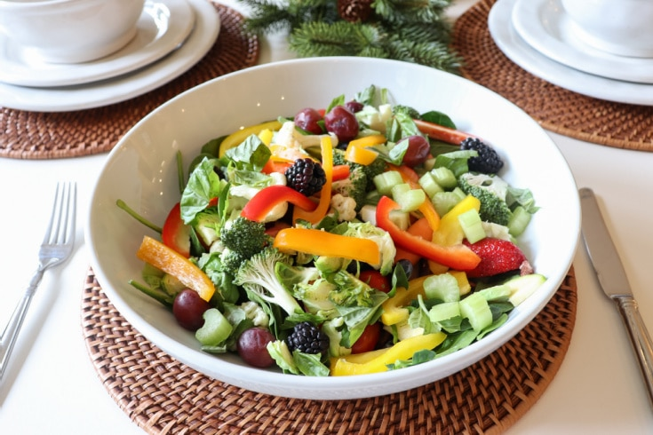 Colorful mix of green vegetables and colorful fruits in white ceramic bowl on rattan placemat