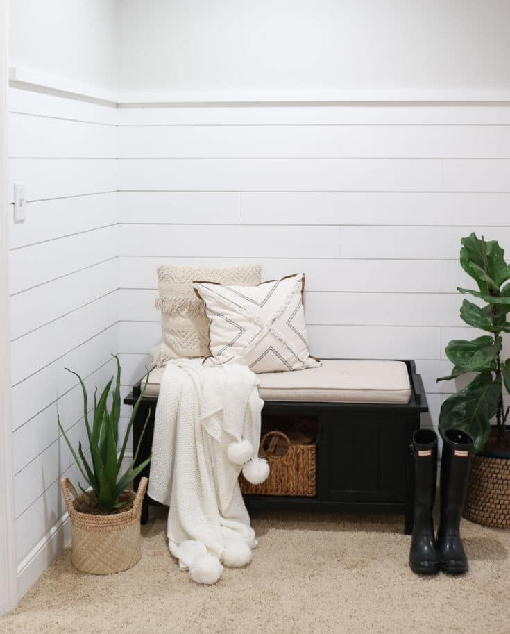 front entryway with white shiplap on walls and farmhouse bench with pillows