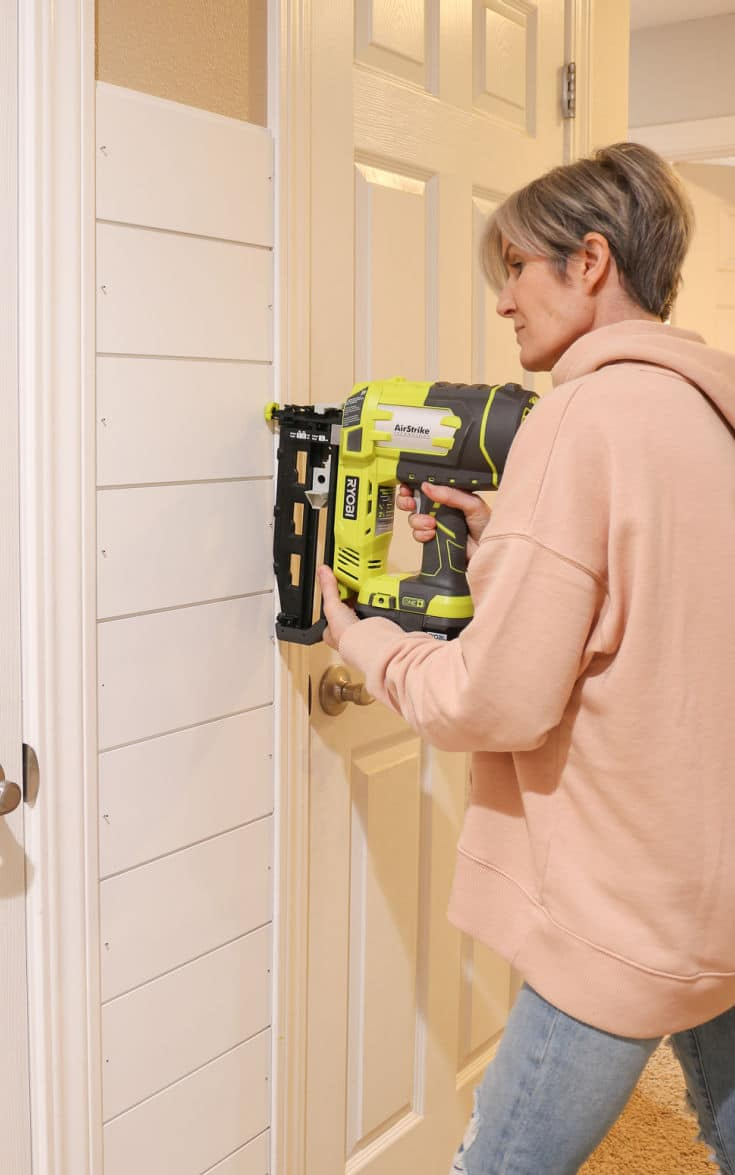 woman using a nail gun on shiplap walls