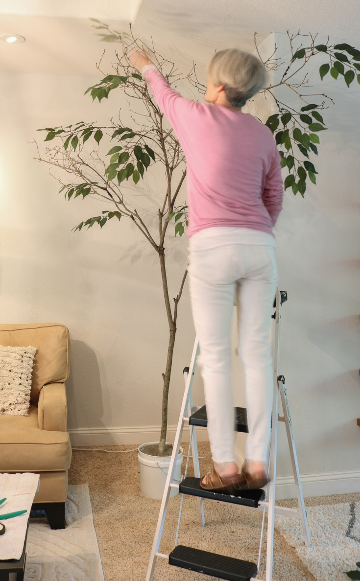 indoor DIY tree project with woman on ladder
