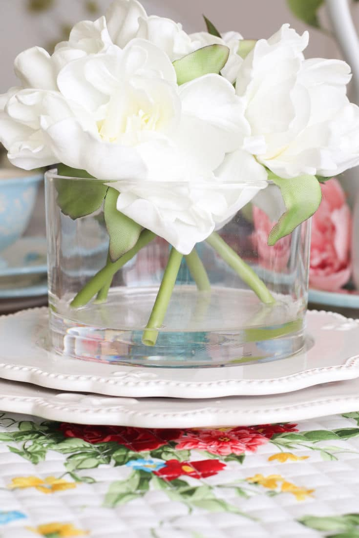 white faux flowers in circular vase on budget designer tablescape