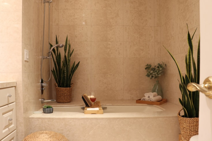 Neutral Natural Boho Bathroom decor with candles, bamboo and woven plant baskets creates relaxing space