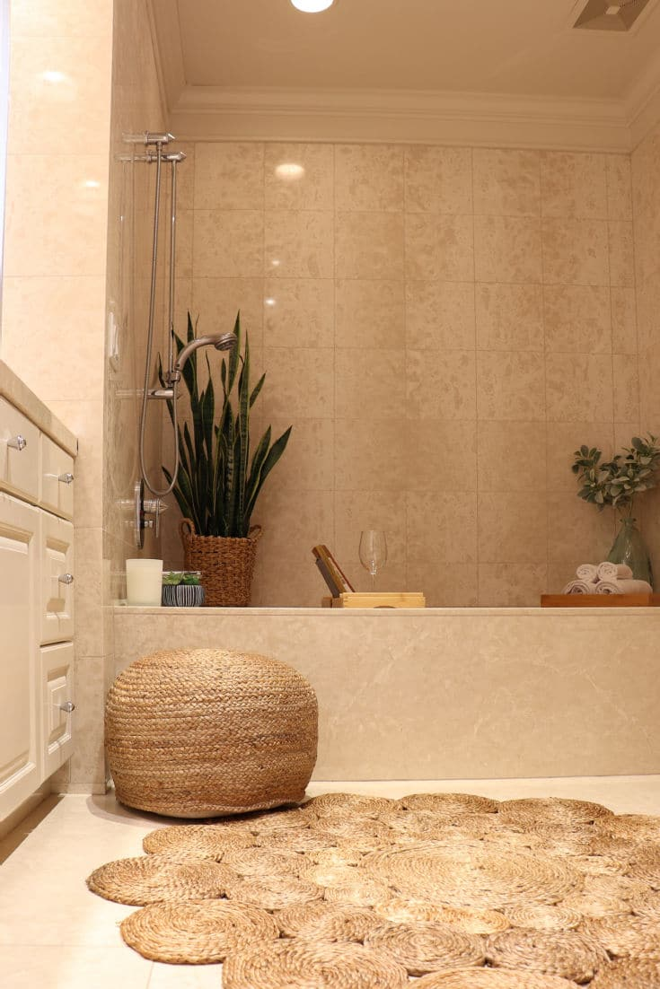 Beautiful bathroom retreat with boho textured rug, woven poof and plants