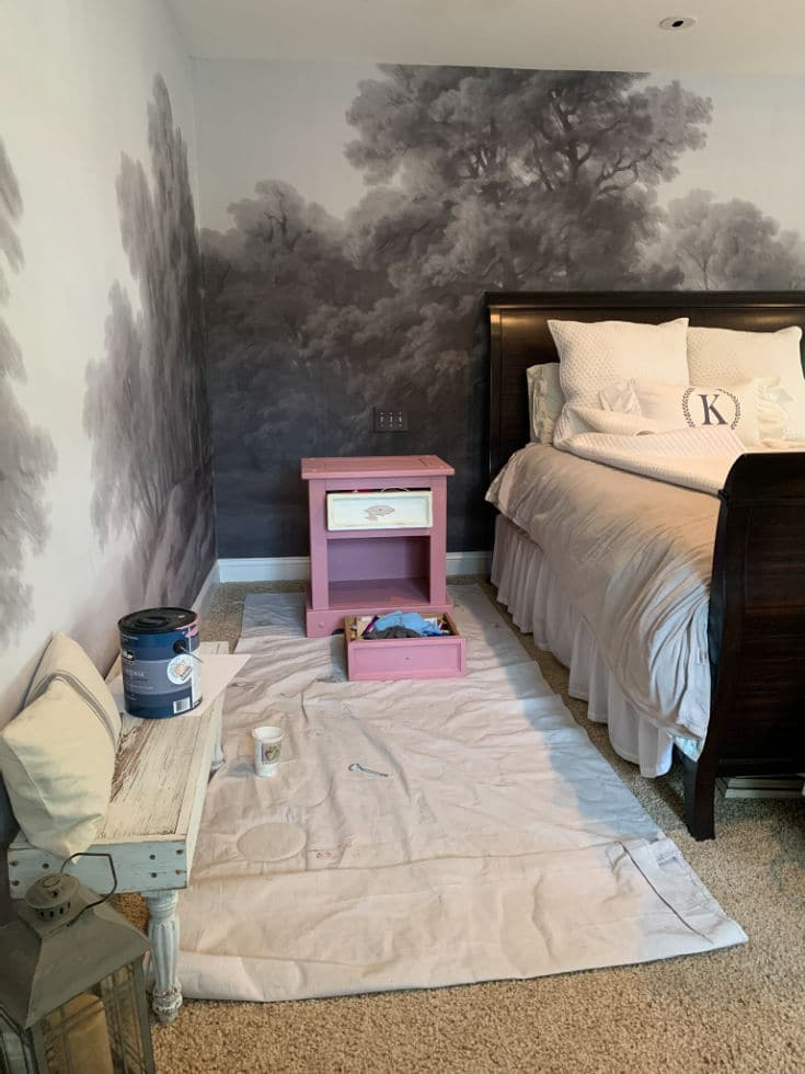 bright pink paint side tables against gray mural