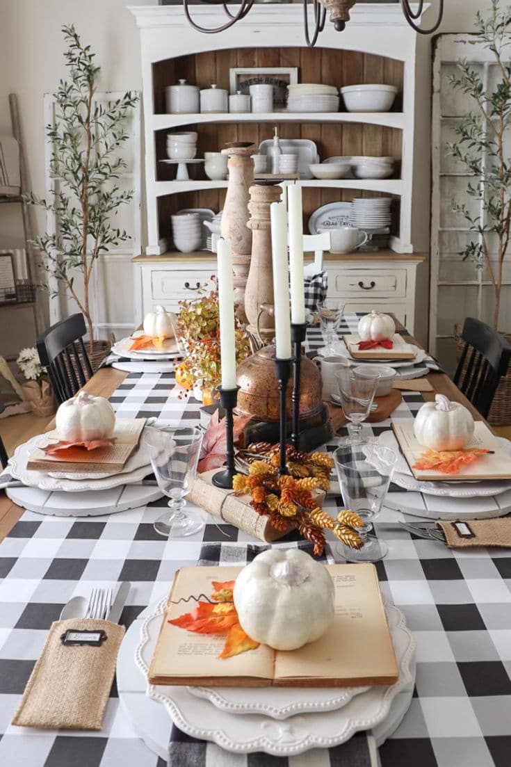 White pumpkins and orange leaves contrast against black and white buffalo plaid table runner