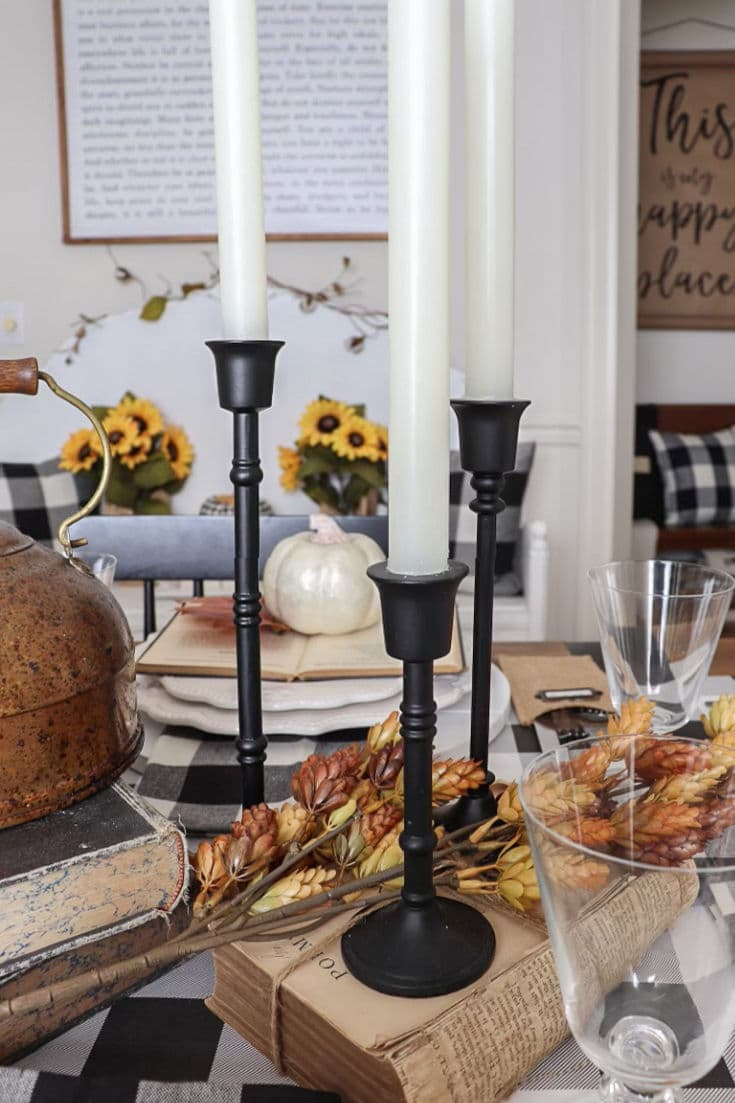 black candlesticks with faux botanicals decorating fall table