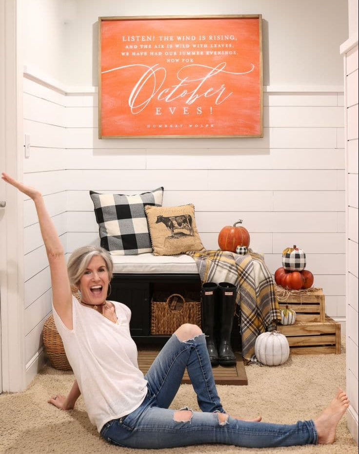 black and white buffalo check pillow pops against orange and white shiplap walls and orange farmhouse sign