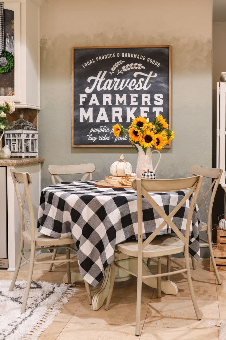 buffalo plaid cafe table pops with sunflowers and farmhouse market sign