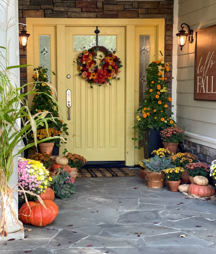 Beautiful fall front door with fall topiary pumpkins and mums