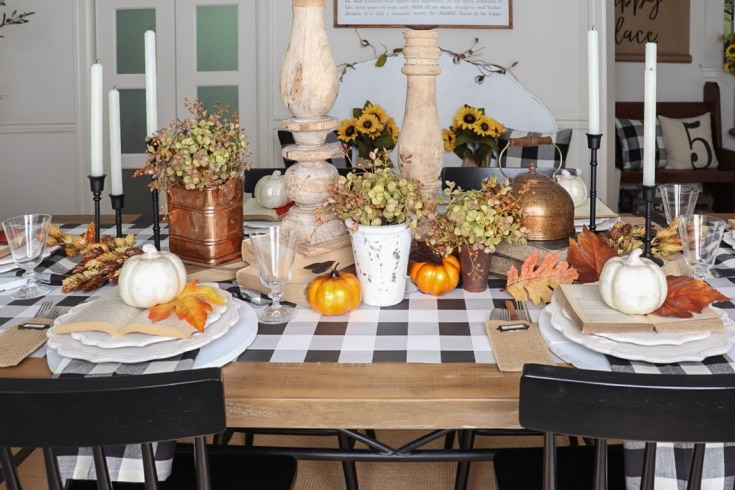 fall table is set with black and white buffalo plaid and natural warm fall colors