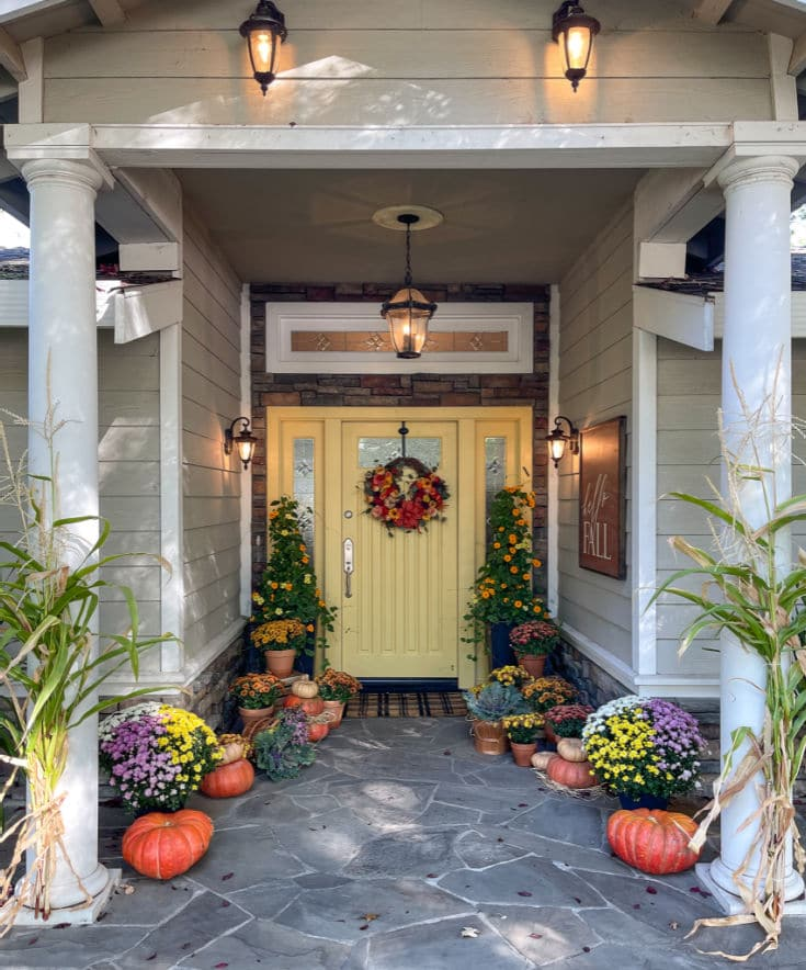 front porch with white columns and gold door with pumpkins and mums decorated for fall