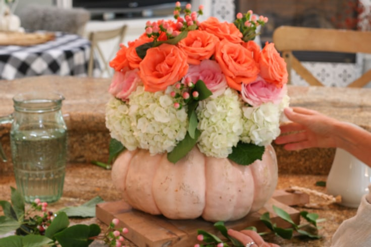 floral bouquet using pumpkin as a vase displays roses and hydrangeas beautifully