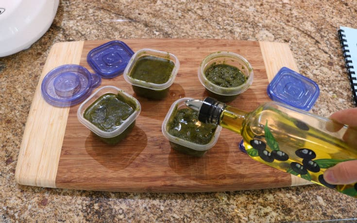 Store single serve containers of basil pesto sauce and seal with olive oil