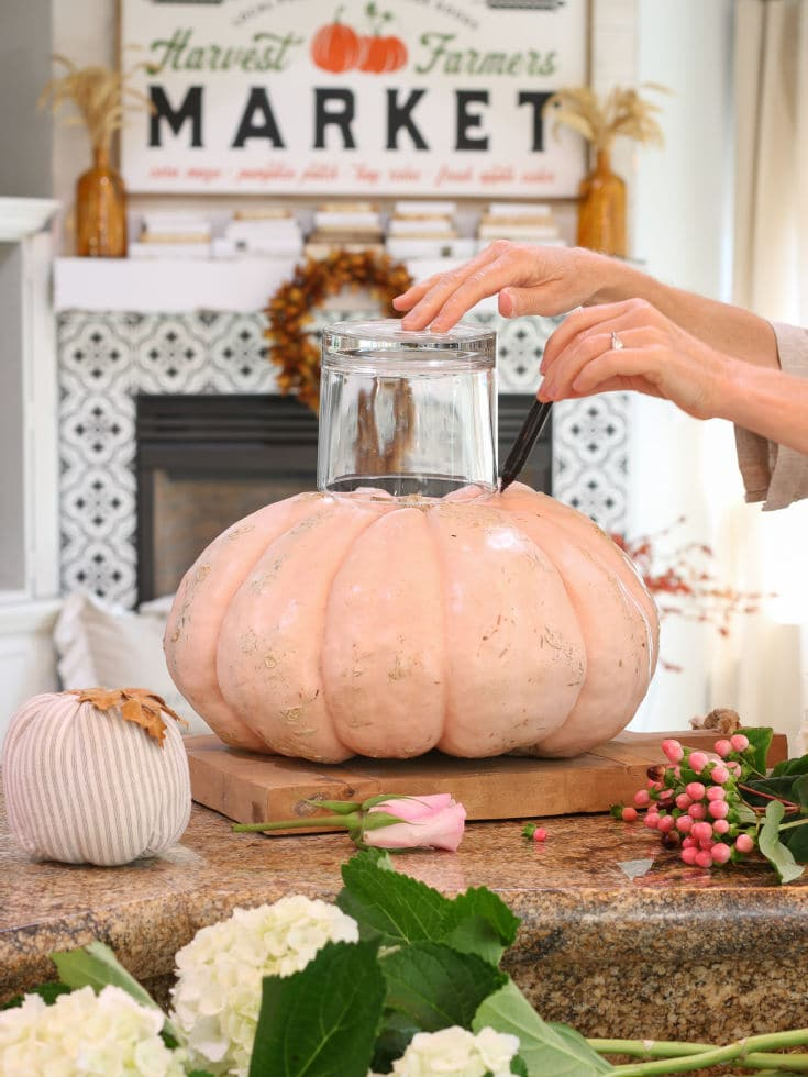 Trace the glass vase around the top of pumpkin to mark where to carve