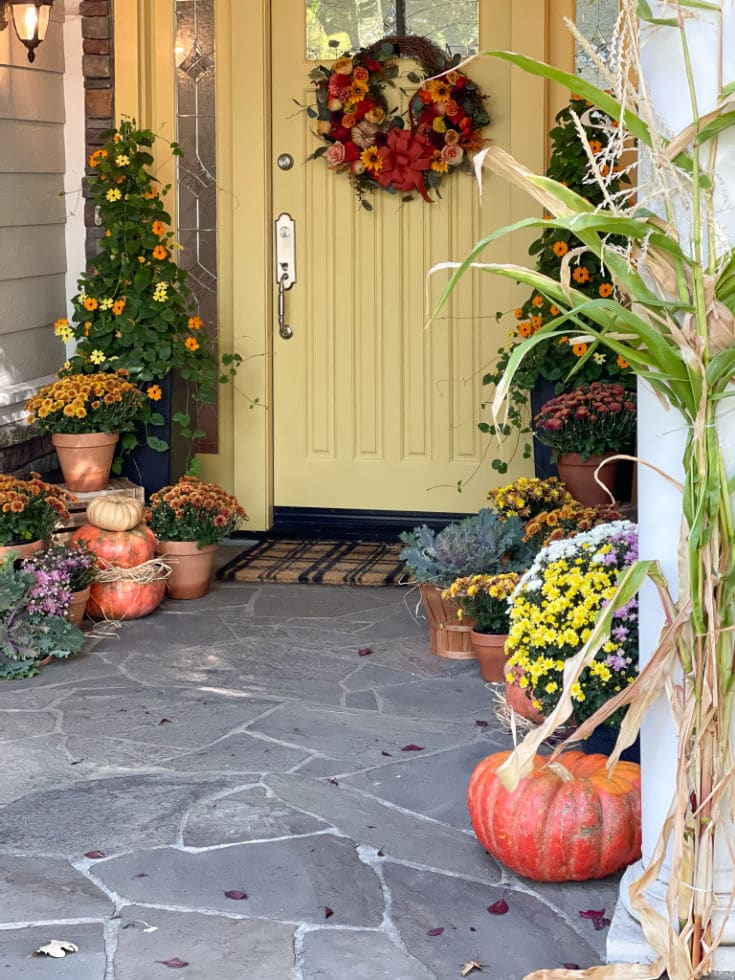 gold painted front door with front porch decorated for fall with pumpkins and mums