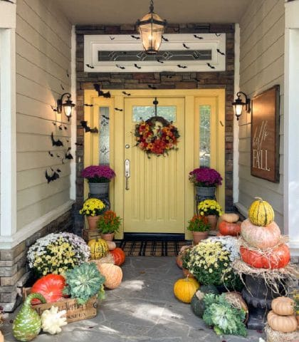 Front door decorated for Halloween with pumpkins and paper bats
