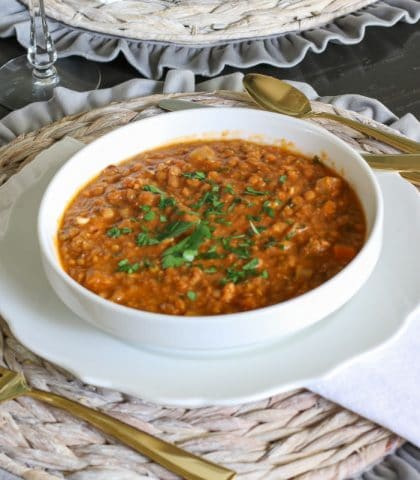 brown lentils in white bowl with Italian parsley garnish on top