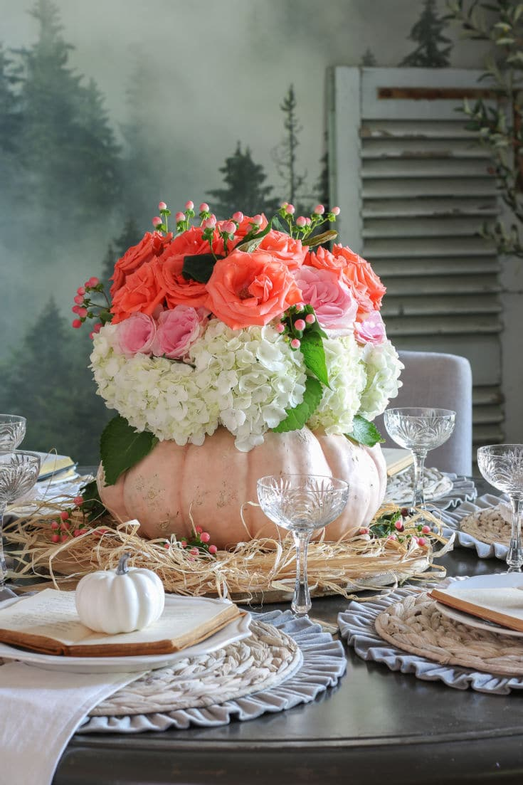pink and coral roses and hydrangeas inside a pumpkin vase create dramatic centerpiece