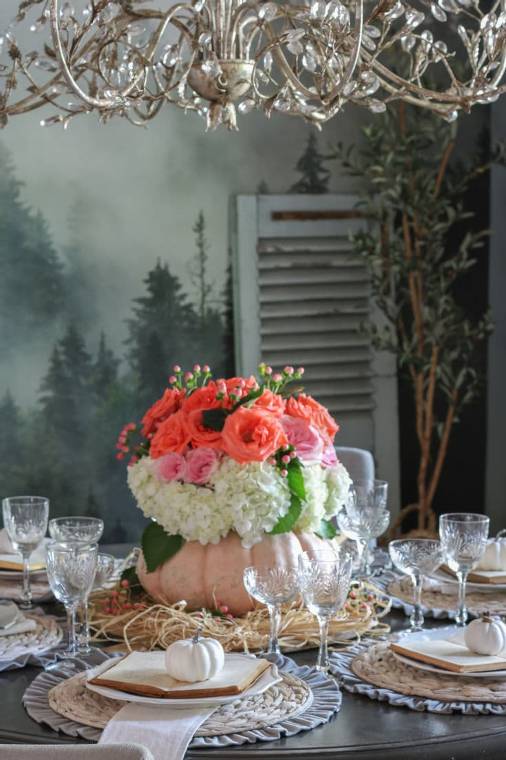 floral pumpkin vase with pink and coral roses and table set with crystal glasses